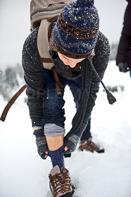 Buy stock photo Shot of a young man pulling up his socks while out on the snow
