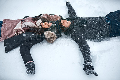 Buy stock photo High angle shot of a couple lying in the snow making snow angels