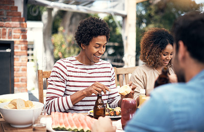 Buy stock photo Shot of a young man having a meal with friends outdoors
