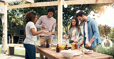 Buy stock photo Shot of a group of friends having a meal together outdoors