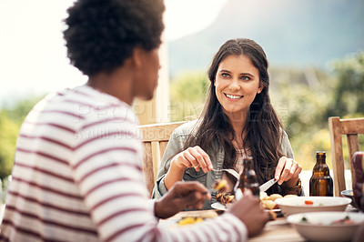Buy stock photo Shot of a young woman having a meal with friends outdoors