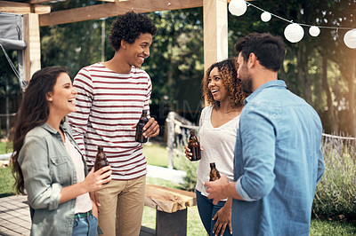 Buy stock photo Shot of a group of friends drinking beer together outdoors