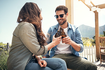 Buy stock photo Shot of a young couple toasting with beers outside