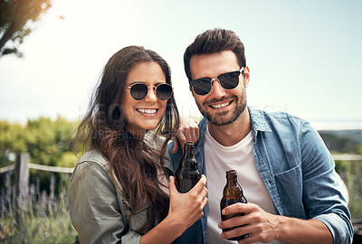 Buy stock photo Portrait of a young couple drinking beer together outdoors