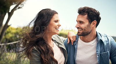 Buy stock photo Shot of a young couple bonding together outdoors