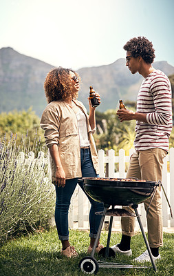 Buy stock photo Shot of a young couple drinking beer while having a barbecue together