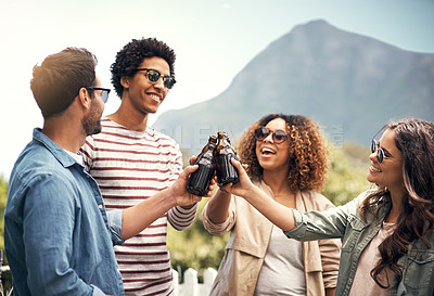 Buy stock photo Shot of a group of friends toasting with beers outside