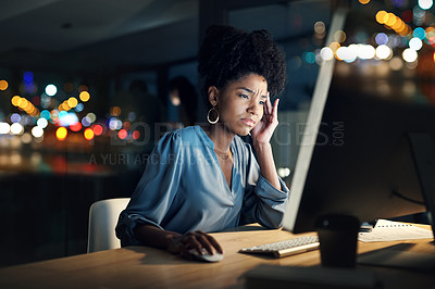 Buy stock photo Shot of a young businesswoman looking stressed out while working late on a computer in an office
