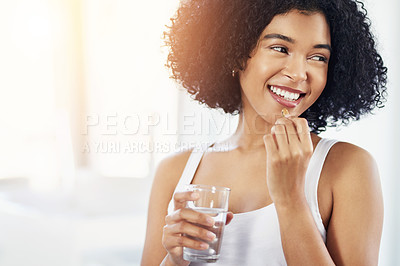 Buy stock photo Cropped shot of a young woman taking her medication
