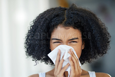 Buy stock photo Cropped shot of a beautiful young woman sneezing into a tissue
