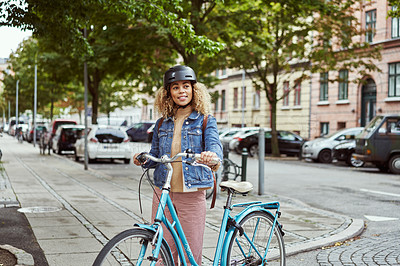 Buy stock photo Shot of an attractive young woman cycling through the city
