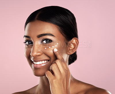 Buy stock photo Studio portrait of a beautiful young woman applying moisturizer to her face against a pink background