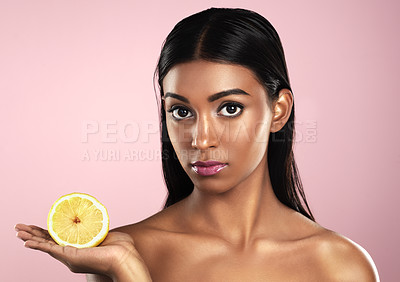 Buy stock photo Studio portrait of a beautiful young woman posing with a half an orange against a pink background