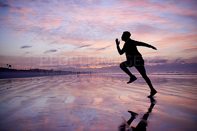 Buy stock photo Silhouette shot of a young man out running at the beach
