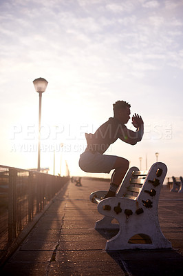 Buy stock photo Shot of a handsome young man taking his exercise routine outdoors