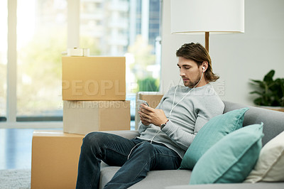 Buy stock photo Cropped shot of a young handsome man listening to music while chilling on the sofa in his new home