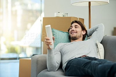 Buy stock photo Cropped shot of a young handsome man watching television in his new home