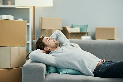 Buy stock photo Cropped shot of a handsome young man taking a nap on the sofa in his new home
