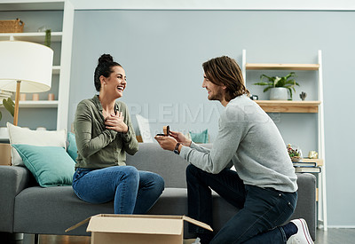 Buy stock photo Cropped shot of a handsome young man proposing to his beautiful young girlfriend on their moving day