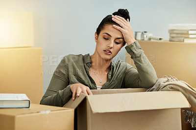 Buy stock photo Cropped shot of a beautiful young woman busy packing on her moving day