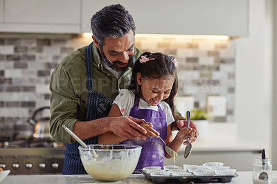 Buy stock photo Cropped shot of a father and his daughter baking in the kitchen