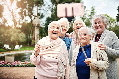 Buy stock photo Shot of a group of senior women taking a selfie with a selfie stick outdoors