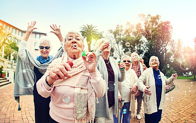Buy stock photo Shot of a group of senior women blowing bubbles together outdoors