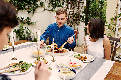 Buy stock photo Cropped shot of a young couple and their friends having lunch outside