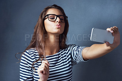 Buy stock photo Studio shot of an attractive young woman taking a selfie against a dark background