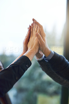 Buy stock photo Cropped shot of a group of unrecognizable businesspeople giving each other a high five in an office