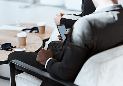Buy stock photo High angle shot of an unrecognizable businessman using his cellphone while sitting in the boardroom during a meeting