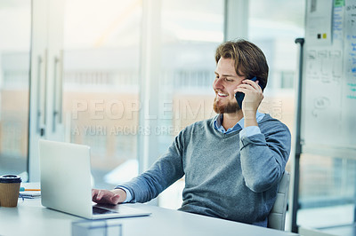 Buy stock photo Shot of a young businessman using a laptop and mobile phone in a modern office