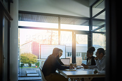 Buy stock photo Shot of a team of young businesspeople having a meeting in the evening at work