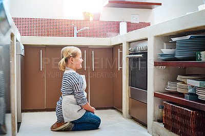 Buy stock photo Shot of an adorable little girl waiting patiently at the oven while her treats bake