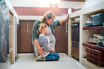 Buy stock photo Shot of an adorable little girl baking with her mother at home