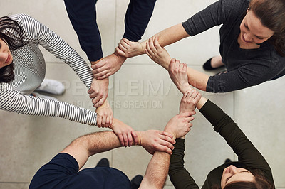 Buy stock photo High angle shot of a group of people linking their arms in solidarity