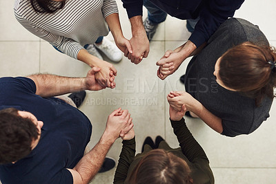 Buy stock photo High angle shot of a group of people holding hands in solidarity