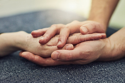 Buy stock photo Cropped shot of two unrecognizable people compassionately holding hands at a table