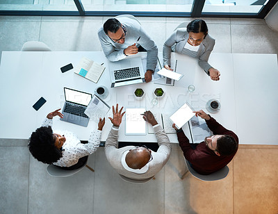 Buy stock photo High angle shot of a group of business colleagues having a meeting in the office boardroom