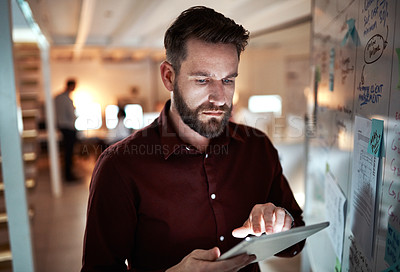 Buy stock photo Cropped shot of a handsome young businessman working on a tablet while standing in his office