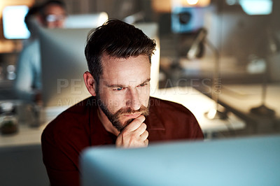 Buy stock photo Cropped shot of a handsome young businessman looking thoughtful while working at his desk in the office