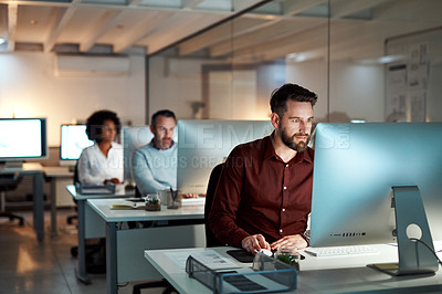 Buy stock photo Cropped shot of a handsome young businessman working at his desk in the office with his colleagues in the background