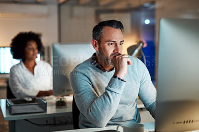 Buy stock photo Cropped shot of a handsome mature businessman looking thoughtful while working at his desk in the office