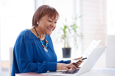 Buy stock photo Shot of a mature businesswoman using a laptop and going over paperwork in a modern office