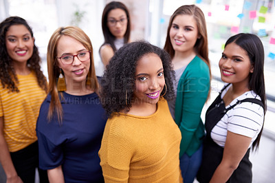 Buy stock photo Portrait of a group of confident businesswomen working together in a modern office