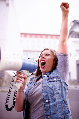 Buy stock photo Cropped shot of a young woman screaming into a loud speaker while protesting in the city