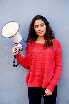 Buy stock photo Cropped shot of a young woman holding a loud speaker against a blue wall in the city
