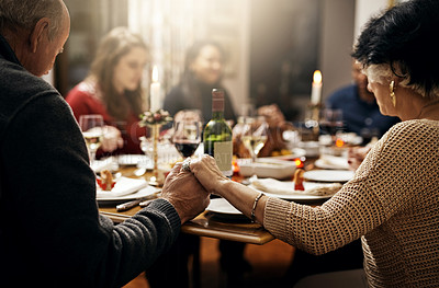 Buy stock photo Shot of family holding hands in prayer before having a Christmas lunch together