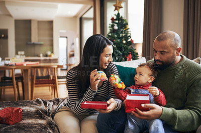 Buy stock photo Cropped shot of a happy young couple giving their daughter her present on Christmas morning