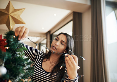 Buy stock photo Cropped shot of an attractive young woman decorating her Christmas tree for the festive season